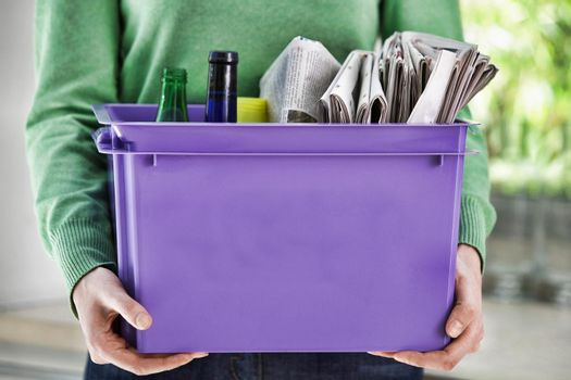 Midsection of a young woman holding recycling container