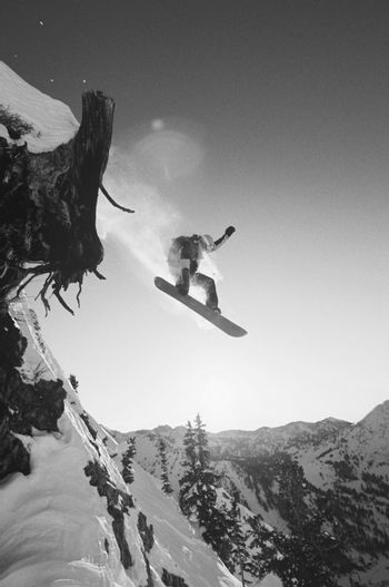 Black and white photo of snowboarder jumping from mountain ledge