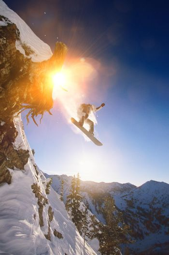 Portrait of snowboarder jumping from mountain ledge
