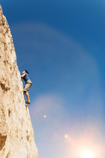 Man Free Climbing on Cliff on sunny day