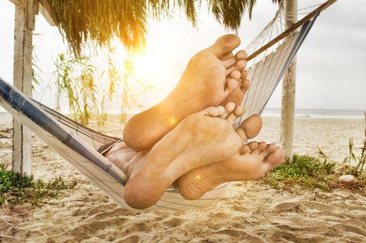 Couple's Feet on Edge of Hammock on Beach