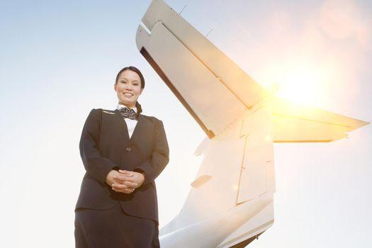 Portrait of Stewardess Beside an Airplane