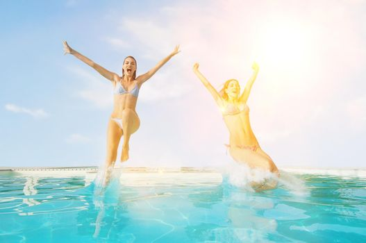 Female friends jumping in pool at resort