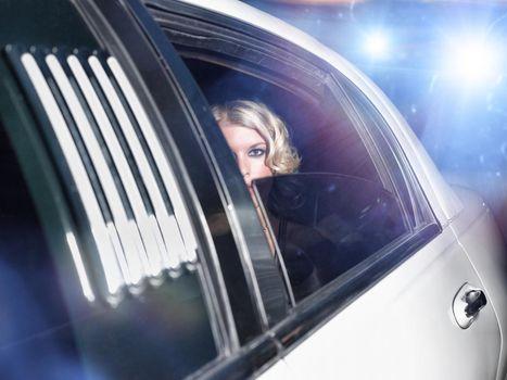 Portrait of beautiful female celebrity inside the limo car