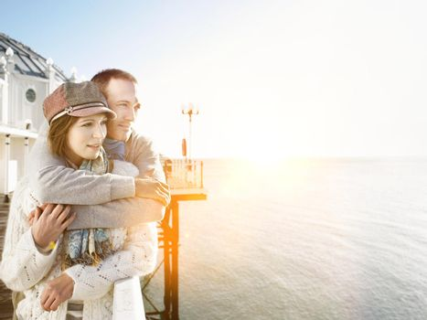 Affectionate couple standing on pier by the sea