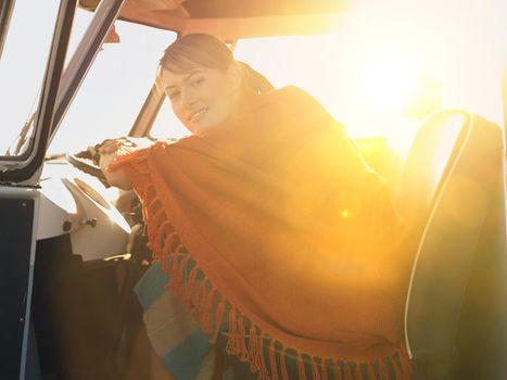 Portrait of woman sleeping with blanket on inside caravan