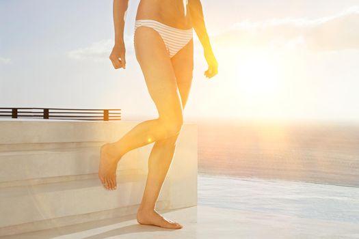Woman walking down steps in bikini