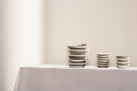 Stacks of plates and cutlery on table