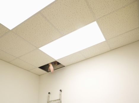 Hand reaching from hole in ceiling