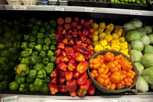 Multicolored bell peppers on display in produce market