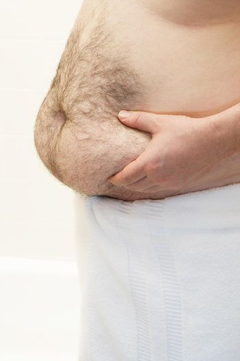 Barechested man with hands on belly