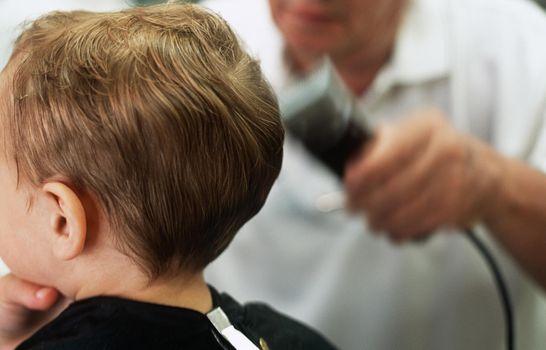 Boy having hair shaved in barbers