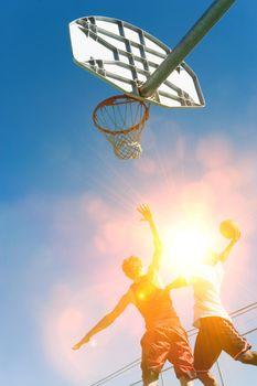 Two men playing basket ball in strong sunshine