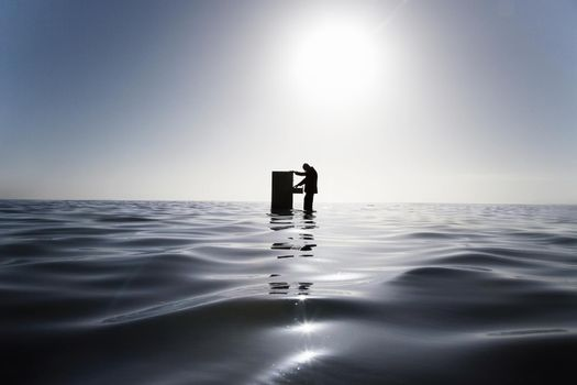 Businessman Standing in the Ocean Searching Through a Filing Cabinet