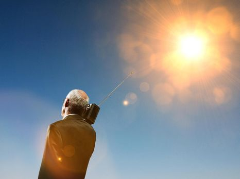 Elderly business man using radio in summer