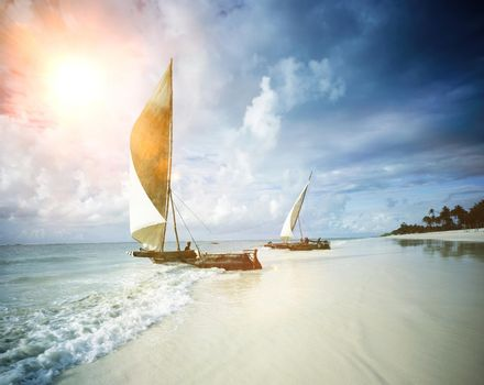 Two sail boats on a beach with sea and the sun
