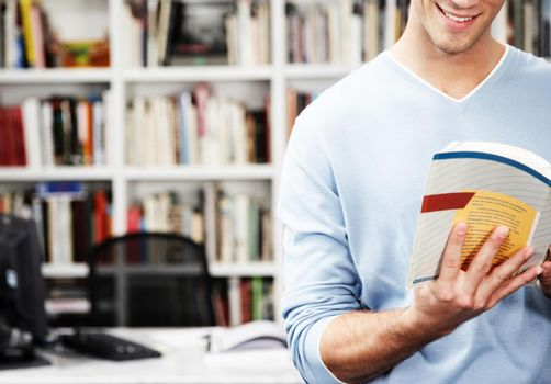 Cropped photo of student reading textbook from home office