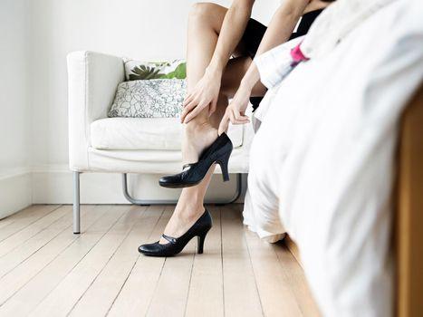 Woman taking off heels in her bedroom