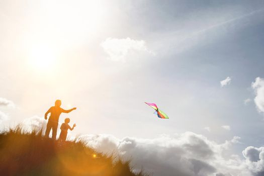 Parent with child playing with kite on the top of the hill
