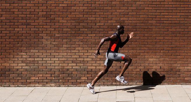 Black male Athlete Sprinting on Sidewalk