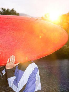 Man carrying kayak outdoors