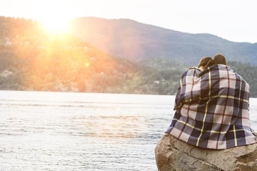 Couple wrapping in blanket sitting by lake