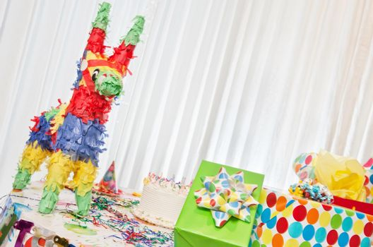 Group of gifts and birthday cake on table including pinata