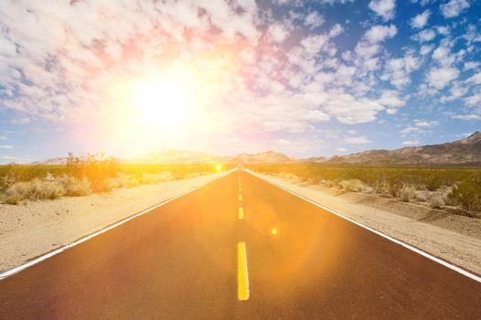 Straight desert road with strong sunshine