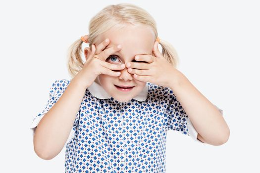 Young girl peering through fingers