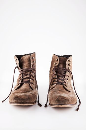 Brown worn vintage boots with untied laces in studio