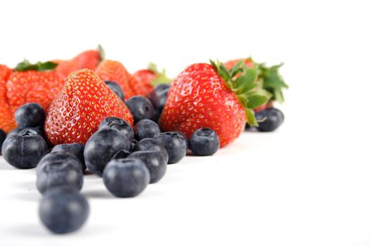 Blueberries and strawberries on white background