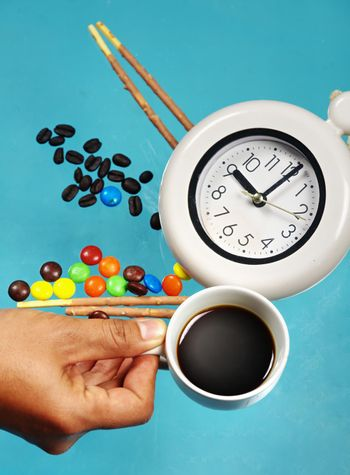 Man hand holding espresso cup with alarm clock on confectionery and sweet candy background.