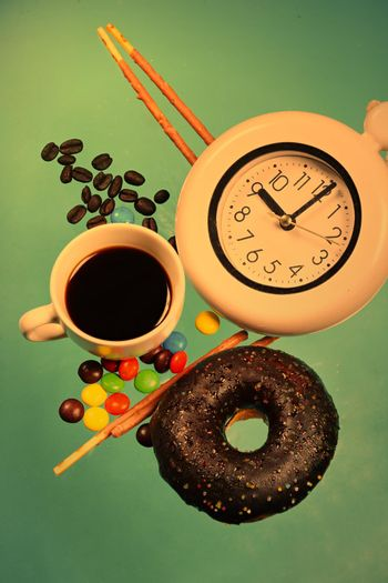 Vertical images of donuts and pastries in bright colors with a cup of hot brewed coffee. Pastel blue background concept sweets and snacks in the morning.