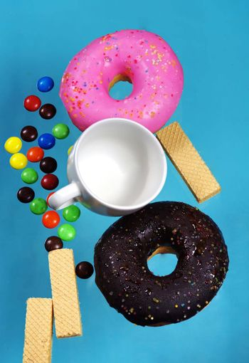 Vertical images of donuts and pastries colorful, pastel blue background. Sweet and snack ideas.