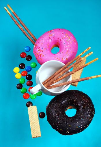 Donuts and pastries colorful background blue pastel dessert and snack concept