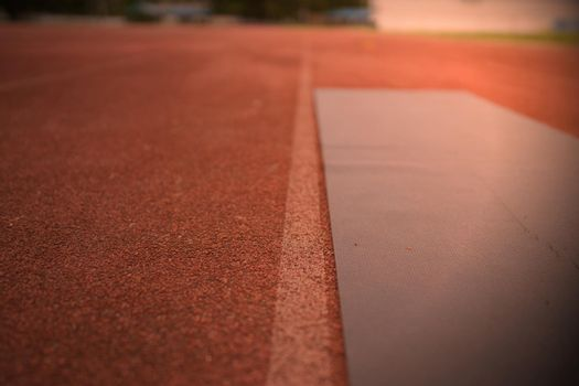 Black yoga mat on the runway of the athletics field, outdoor exercise concept.