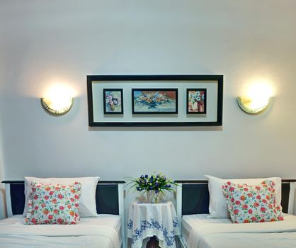 The luxurious twin bedroom features white linens and floral pillowcases.