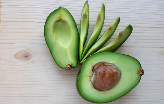 Slices of ripe avocado lie on a light cutting board.