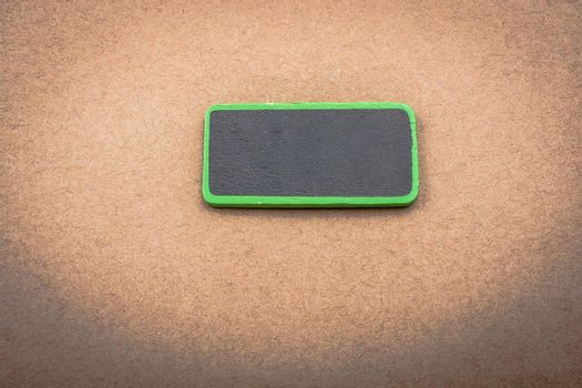 Small green sided black noticeboard on wooden background