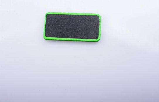 Small green sided black noticeboard on white background
