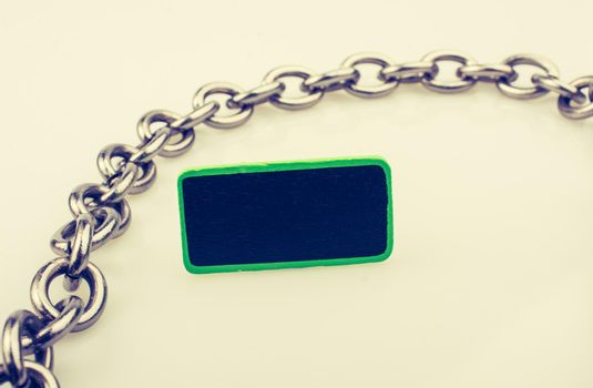Small green sided black noticeboard surrounded by chain on white background