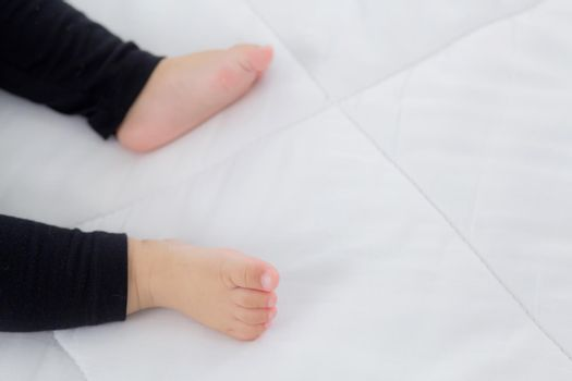 Closeup foot of asian little baby girl sleeping on bed in the bedroom at home, newborn napping with cozy and relax, infant innocence in bedtime, happy toddler cute, growth of child and emotion.