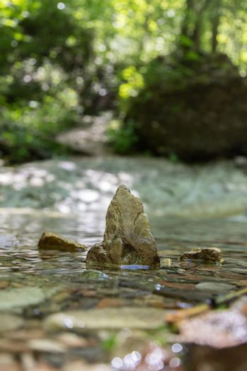 Spirituality and nature concept: Small stone in the fresh and clean water of a mountain creek