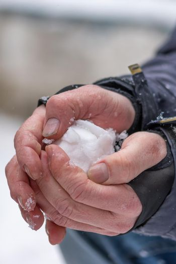 Vertical shot of hands forming a snowball
