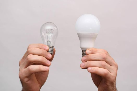 Two lamps in the hands of a man. Incandescent light bulb and LED light bulb in your hands. Close-up. On a white background. In isolation.