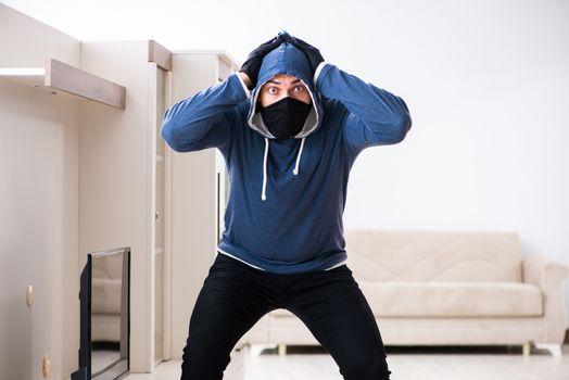 Man burglar stealing tv set from house