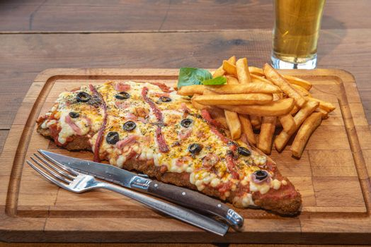 Typical Neapolitan Milanese typical food from Argentina and Uruguay served with French fries and on wooden board