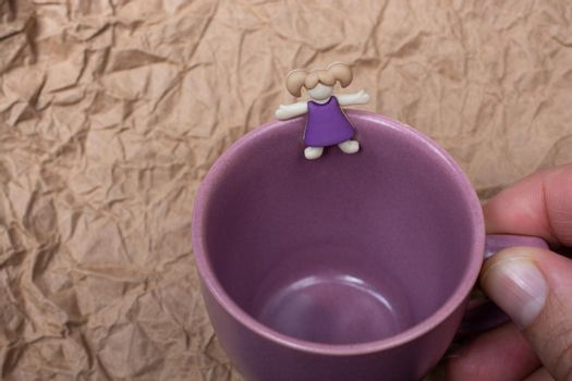 Miniature girl figurine at the edge of  mug cup