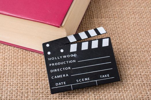 Movie clapper beside a book on a canvas background