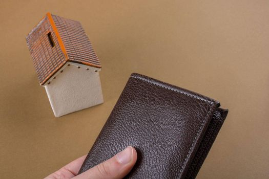 Little model house  beside a wallet in hand